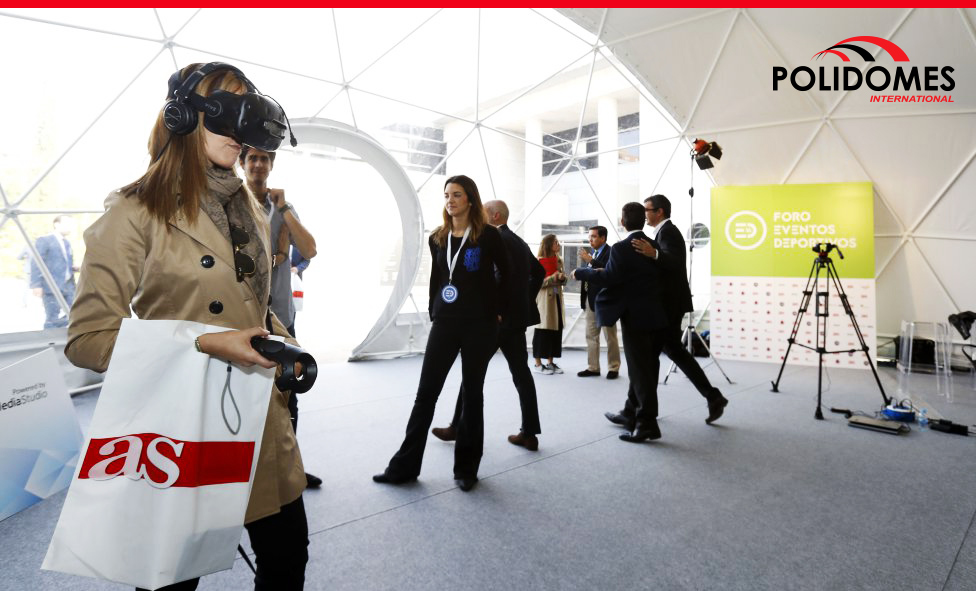 people testing virtual reality with 3D glasses in geodesic event tent